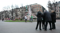 People photograph with monument to the poet Johan Runeberg at Esplanadi Square Stock Footage