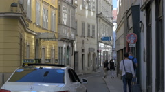 Walking and driving on a narrow street in the first district of Vienna Stock Footage