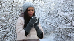 Beautiful happy girl warms up with hot tea. Snow covered trees in winter park Stock Footage