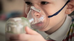 The little boy makes treatment procedure by an inhaler where upper respiratory t Stock Footage