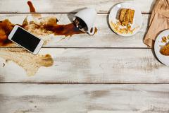 Cup of coffee spilled on wooden table Stock Photos