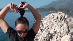 Woman tries to cuts her hair 2 Stock Footage