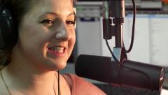 Radio presenter speaks into the microphone on the background monitor close-up - stock footage