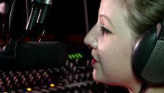 Radio presenter close-up of a girl speaking into the microphone in a studio - stock footage