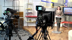 Studio news channel equipment and a woman news performer backstage Stock Footage