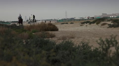 Arab Horsemen in Bahrain. Wide angle with desert context. - stock footage