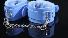 Stock Video Footage of blue leather handcuffs in black background. sex toy