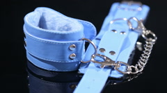 Blue leather handcuffs in black background. sex toy Stock Footage