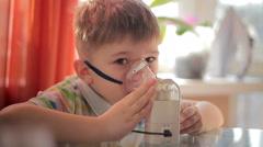 The little boy makes treatment procedure by an inhaler where upper respiratory t Stock Footage