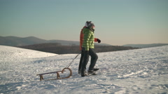 Best ager couple walking up hill with sled Stock Footage
