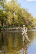 woman fishing in the river in spring - stock photo