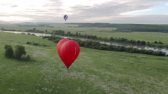 Flight of behind red hot air balloon - stock footage