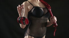Busty girl in lingerie shows Red handcuffs. on black background. sex toy. red - stock footage