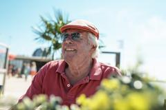 Happy fashionable senior man in tropical sunshine - stock photo
