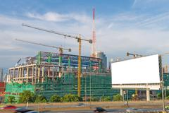 Blank billboard ready for new advertisement on road with Construction site - stock photo