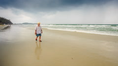 Bearded Old Man in Hat Goes along Wet Sand by Wave Surf Stock Footage