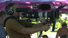 Cameraman shooting footage with telephoto lens Stock Footage