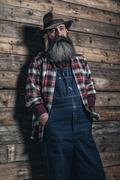 Vintage worker man with long gray beard in jeans dungarees. Standing in front Stock Photos
