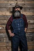 Smoking vintage worker man with long gray beard in jeans dungarees. Standing  Stock Photos