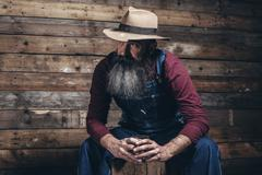 Vintage worker man with long gray beard in jeans dungarees holding whiskey. S Stock Photos