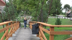 Woman walk on wooden bridge hanging on rusty chains in park. 4K Stock Footage