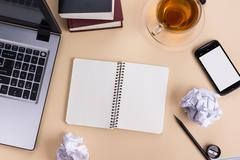 Office table desk with supplies, white blank note pad, cup, pen, pc, crumpled Stock Photos