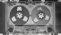 Tape with metal reels in recorder is rapidly rewound. Black and white negative - stock footage