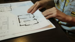 young woman architect chooses the blueprint sheets with layouts and drawings of - stock footage