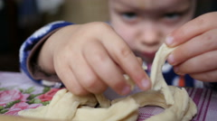 Little kid girl have fun playing with dough in a kitchen stretch it and tear  Stock Footage