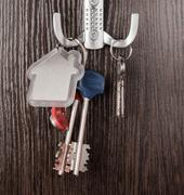 Keys and House shaped keychain on wooden background Stock Photos