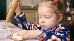 Little kid girl playing with dough with fingers and rolls with a rolling pin  Stock Footage