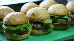 Fresh cooked hamburgers in restaurant kitchen are ready for order Stock Footage