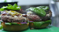 Cooking hamburger - ingredients are buns vegetables and grilled meat Stock Footage
