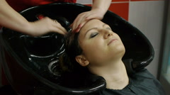 Hairdresser washing a clients hair in a modern basin in her hairdressing salon - stock footage