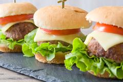Burgers with meat, lettuce, cheese and tomato Stock Photos