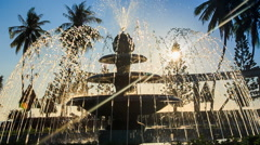Closeup round fountain operates changing jets in tropical park Stock Footage