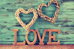 two hearts and wooden letters forming the word love - stock photo
