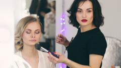 woman applying make-up by make-up artist. Puts the powder - stock footage