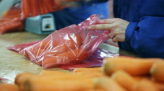 People pack and packing carrots in packages for resale Stock Footage