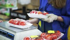Woman sticks price tags on containers with tomatoes Stock Footage