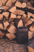 Firewood pile and plastic oil canister Stock Photos