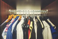 Variety of clothes hanging in wooden wardrobe Stock Photos