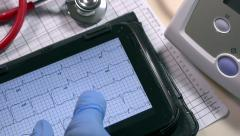 Examining an ECG graph on a digital tablet. Stock Footage