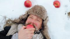 Portrait of a bearded man with an apple in the winter. Stock Footage