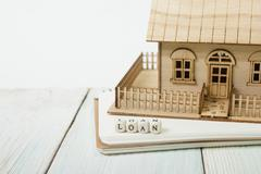 Wooden blocks spelling the word LOAN and model house on table - stock photo