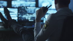 Security officer is relaxing at a computer desk while drinking coffee in office - stock footage