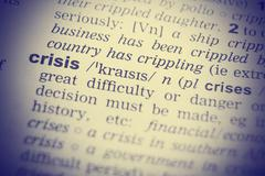 Stock Photo of Close up shot of the word crisis from a dictionary