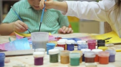 Little children are painting at the table Stock Footage