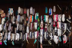 Lots of different shoes hanging in the showcase on market - stock photo