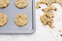 Four chocolate chip cookies on a baking tray - stock photo